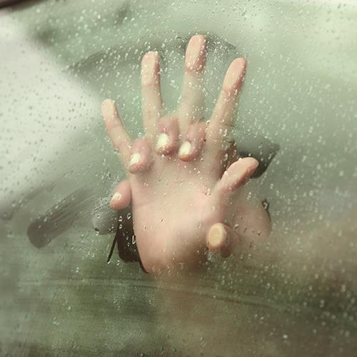 Hands pressed against steamed up car window